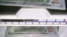 La máquina del contador del dinero electrónico está contando está contando los billetes de banco americanos de los dólares de EE. almacen de video