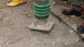 La máquina del equipo del rodillo del compresor de la placa aplana el pavimento en el emplazamiento de la obra en ciudad de la ca metrajes