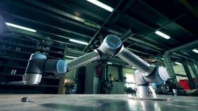 La máquina del metal funciona con los engranajes en una tabla en una planta almacen de video
