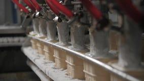 La máquina del robot vierte automáticamente el helado en tazas de una oblea Las líneas automáticas del transportador para la prod almacen de metraje de vídeo