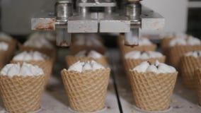 La máquina del robot vierte automáticamente el helado y el chocolate en tazas de una oblea Las líneas automáticas del transportad almacen de metraje de vídeo