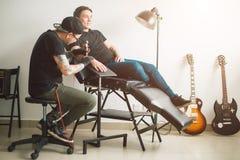 La máquina del tatuaje hace el dibujo en la mano masculina Fotografía de archivo libre de regalías