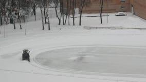 La máquina del tractor despeja la nieve en la pista de hielo metrajes