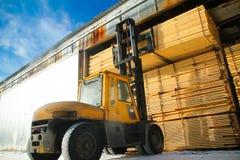 La máquina está levantando la madera de construcción Imagenes de archivo