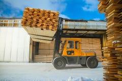 La máquina está levantando la madera de construcción Imagen de archivo