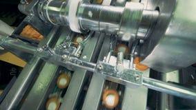 La máquina industrial del metal está añadiendo la capa poner crema a las galletas metrajes