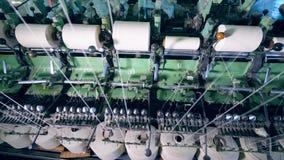 La máquina industrial está desenrollando los carretes de costura Equipo de la fábrica de la materia textil almacen de metraje de vídeo