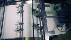 La máquina industrial se está trasladando la forma de las hojas de papel una pila a una bandeja almacen de video
