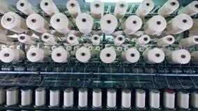 La máquina moderna de la fábrica de la materia textil funciona con los carretes con la fibra blanca metrajes