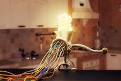 La máquina remilgada está moliendo encima de una lámpara Imagen de archivo libre de regalías
