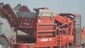La máquina segador arrastrada tractor monta en un campo polvoriento y las patatas de la recogida metrajes