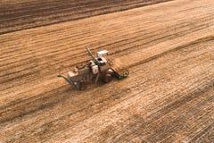 La máquina segador que trabaja en campo y siega trigo ucrania Silueta del hombre de negocios Cowering Imagen de archivo