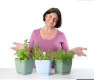 La más vieja mujer linda muestra los potes con los almácigos de hierbas Foto de archivo