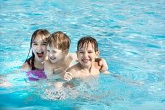 La más viejos hermana y hermanos menores tres están nadando y se están divirtiendo en la piscina con agua azul imagen de archivo libre de regalías