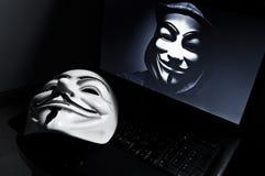 La máscara de la venganza en computeur con el miembro anónimo encendido sreen Esta máscara es un símbolo bien conocido para el ha Imágenes de archivo libres de regalías
