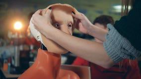 La máscara humana está consiguiendo puesta sobre una cabeza cibernética por una señora almacen de metraje de vídeo