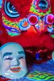 La máscara sonriente del tostador de palomitas de maíz y el traje rojo de la danza de león se preparan para el lomo Imagen de archivo libre de regalías