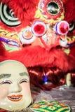 La máscara sonriente del tostador de palomitas de maíz y el traje rojo de la danza de león se preparan para el lomo Imágenes de archivo libres de regalías
