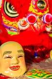 La máscara sonriente del tostador de palomitas de maíz y el traje rojo de la danza de león se preparan para el lomo Foto de archivo libre de regalías