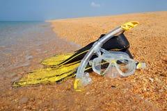 La máscara y las aletas en la playa Fotos de archivo