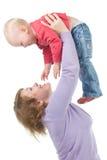 La mère élève vers le haut un descendant gai Image stock