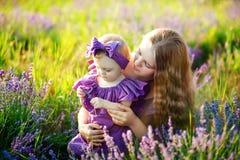 La mère étreint sa petite fille dans les rayons du coucher de soleil, portant de longues robes de lilas Photographie stock