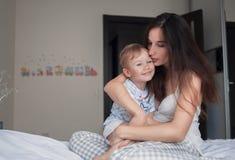 La mère étreint son fils sur le lit Photographie stock libre de droits