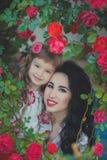 La mère adorable des meilleures amies avec les poils noirs foncés et la fille mignonne de bébé avec les poils blonds et la pose r Photographie stock libre de droits