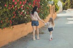 La mère adorable des meilleures amies avec les poils noirs foncés et la fille mignonne de bébé avec les poils blonds et la pose r Image stock