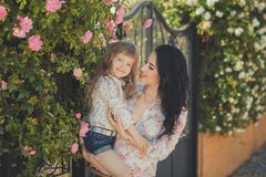La mère adorable des meilleures amies avec les poils noirs foncés et la fille mignonne de bébé avec les poils blonds et la pose r Photo libre de droits