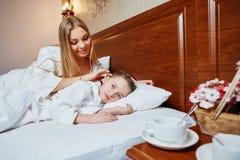 La mère affectueuse repasse la fille se situant dans un lit sur la tête Images libres de droits