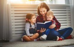 La mère affiche le livre aux enfants Images libres de droits