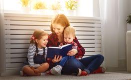 La mère affiche le livre aux enfants Photos stock