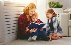 La mère affiche le livre aux enfants Image stock
