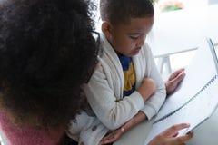 La mère aidant son fils dans le sien étudie Image libre de droits