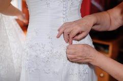 La mère aide la jeune mariée à porter la robe dans le jour du mariage Images stock