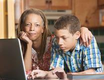 La mère aide le fils adolescent avec des devoirs dans la cuisine photographie stock libre de droits