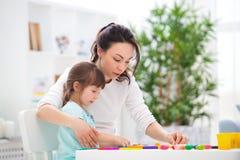 La mère aide une petite fille à sculpter des figurines de pâte à modeler Créativité du ` s d'enfants Famille heureux images stock