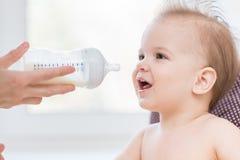 La mère alimente le bébé d'une bouteille de lait photo libre de droits