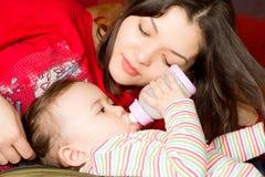 La mère alimente sa chéri avec une bouteille Photographie stock libre de droits