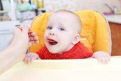 La mère alimente ses petits 6 mois de fille photos libres de droits