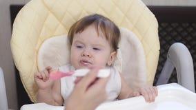 La mère alimente un petit bébé d'une cuillère à la purée de pommes de terre chemise de nourriture salie par bébé clips vidéos