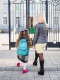 La mère a amené sa fille à l'école, vue par derrière, famille de concept images stock