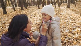 La mère applique le lustre sur les lèvres du ` s de fille en parc d'automne banque de vidéos