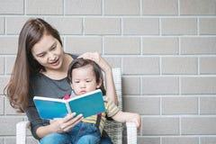La mère asiatique de plan rapproché enseigne son fils à lire un livre sur la pierre Photo libre de droits