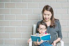 La mère asiatique de plan rapproché enseigne son fils à lire un livre sur la pierre Photographie stock libre de droits