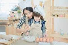 La mère asiatique et sa fille préparent la pâte Photographie stock libre de droits