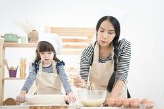 La mère asiatique et sa fille préparent la pâte Photo libre de droits