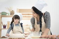 La mère asiatique et sa fille préparent la pâte Photo stock