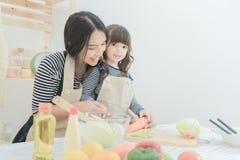 La mère asiatique et sa fille préparent la salade saine de nourriture Photographie stock libre de droits